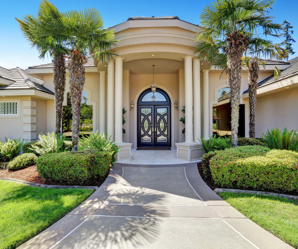 Suburban luxury house with column porch and arched entrance door. Northwest USA